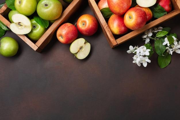 さびた背景に白い花の枝と木製の箱で熟した赤と緑のリンゴ。テキスト用のスペースがある上面図。