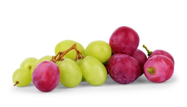 白に分離された熟した赤と緑のブドウ