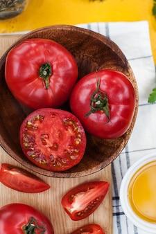 잘 익은 빨간색과 분홍색 토마토를 통째로 자르고 에코마켓을 위한 나무 판자 음식 사진