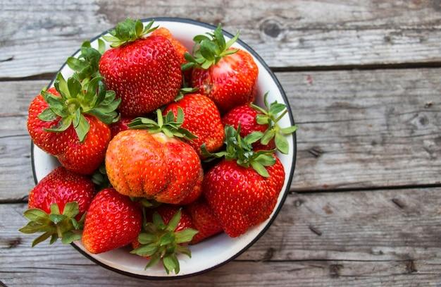 잘 익은 빨간색과 딸기, 접시에 테이블에 수확