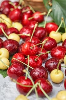 Спелые красные и желтые вишни на сером фоне
