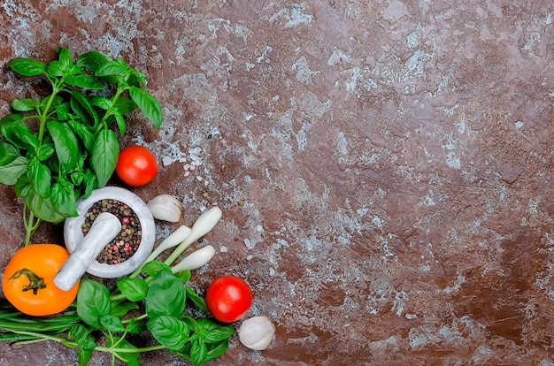 暗い石の背景に熟した赤と黄色のトマト、ネギとバジル、ニンニク、塩とスパイス。上面図、コピースペース。