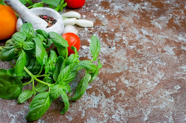 Спелые красные и желтые помидоры, зеленый лук и базилик, чеснок, соль и специи