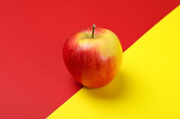 2 トーンの背景に熟した赤いリンゴ