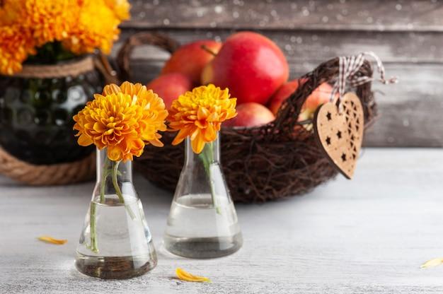 Спелые красные яблоки и желтые хризантемы на деревенском столе. осенний декор с сердцем