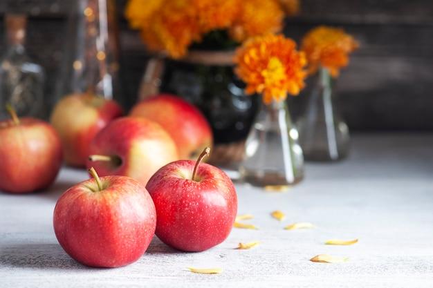 Спелые красные яблоки и желтые хризантемы на деревенском столе. осенний декор