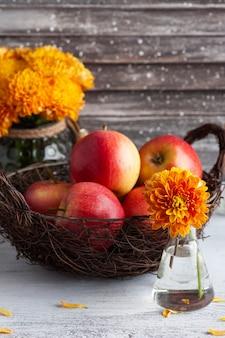 素朴なテーブルに熟した赤いリンゴと黄色の菊