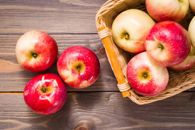 Ripe red apples and basket with apples on a wooden table. copyspace
