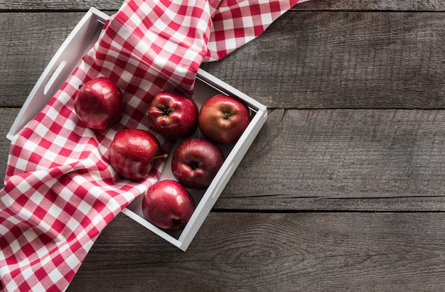 Ripe red apples in birch-box on wooden board with red checkered napkin around and copy space.