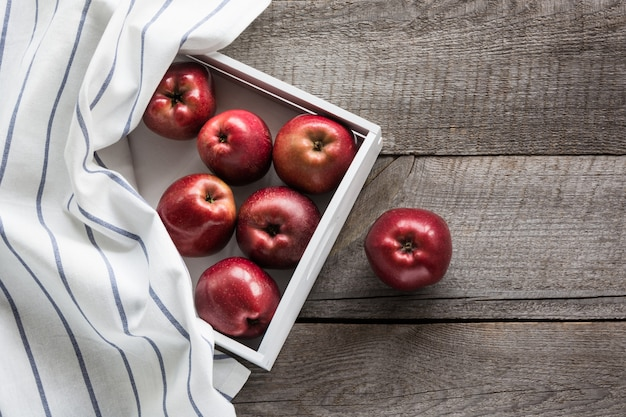 Ripe red apples in birch tray on board with red checkered napkin around