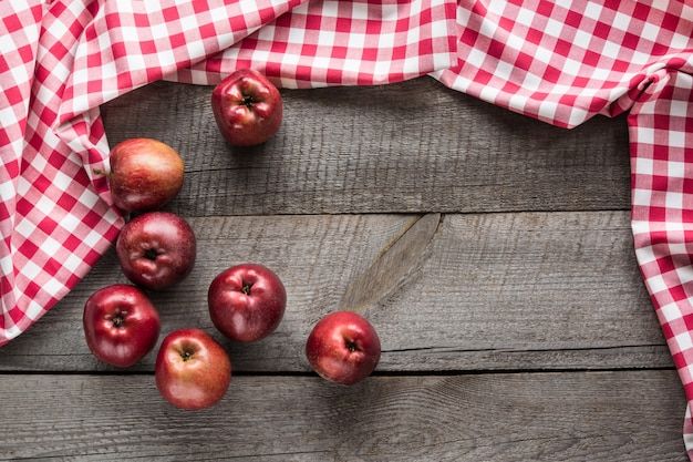 Ripe red apples on board with red checkered napkin around and copy space.
