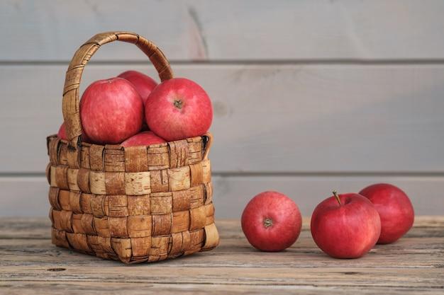 古いボード上のヴィンテージの籐のバスケットに庭から熟した赤いリンゴ