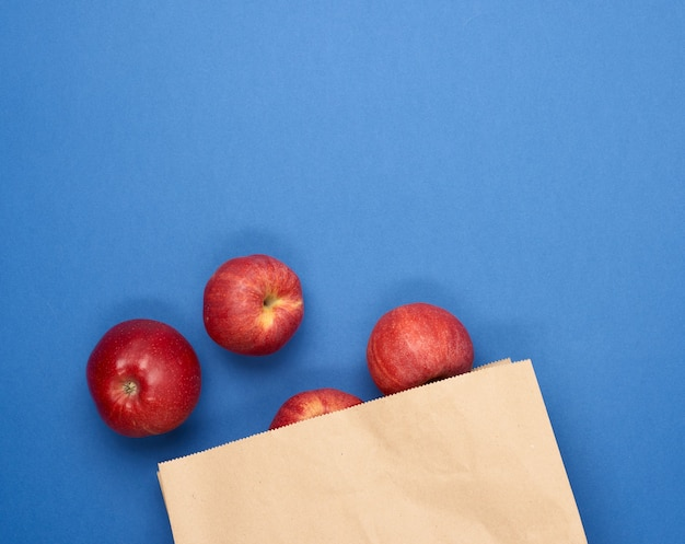 Спелые красные яблоки в коричневом бумажном пакете