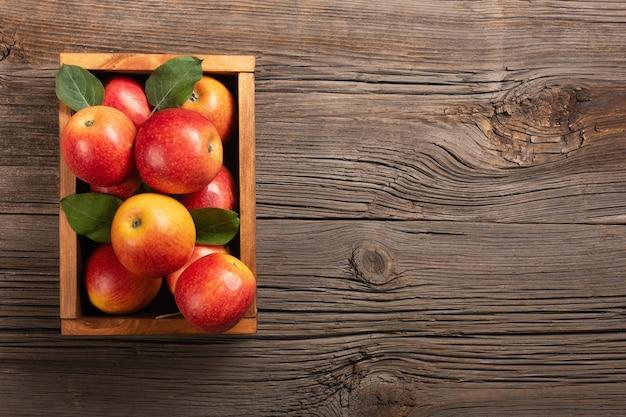 木製のテーブルの上の木製の箱に熟した赤いリンゴ。テキスト用のスペースがある上面図。