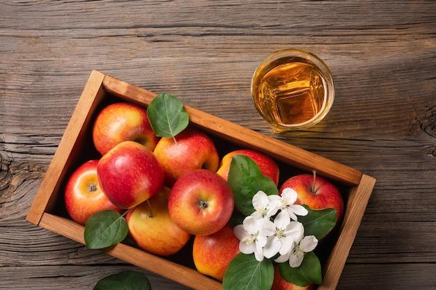 白い花の枝と木製のテーブルの上のフレッシュジュースのガラスと木製の箱で熟した赤いリンゴ。上面図。