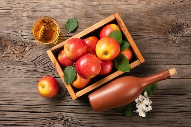 白い花の枝、ガラス、木製のテーブルにサイダーのボトルと木製の箱に熟した赤いリンゴ。テキスト用のスペースがある上面図。