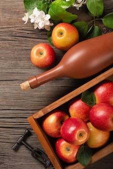 白い花の枝、ガラス、木製のテーブルにサイダーのボトルと木製の箱に熟した赤いリンゴ。上面図。