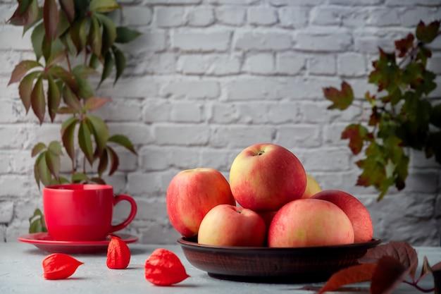 レンガの壁の背景にキッチンテーブルの上の熟した赤いリンゴ
