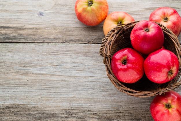 Спелые красные яблоки на деревянных фоне.