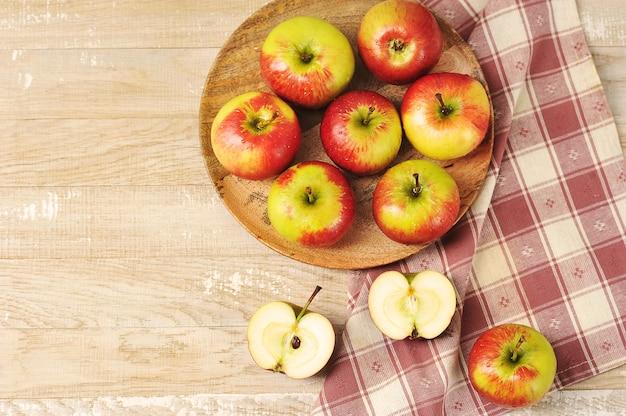 素朴な木製の背景の木製プレート上面図に熟した赤いリンゴ