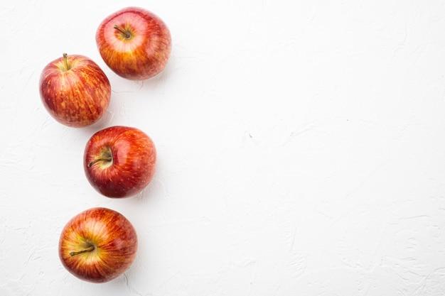Набор спелых красных яблок на фоне белого каменного стола, плоская планировка, вид сверху, с копией пространства для текста