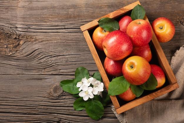木製のテーブルの上の木製の箱に白い花の枝を持つ熟した赤いリンゴ。テキスト用のスペースがある上面図。