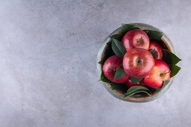 Спелые красные яблоки с листьями в миске на каменном фоне.