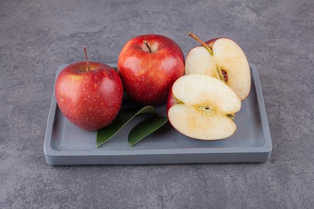 Спелые красные яблоки с листьями на каменной поверхности.