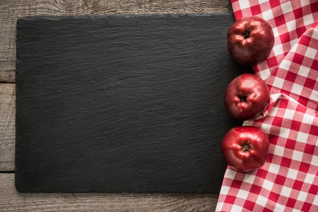 Ripe red apples on wooden board with red checkered napkin around