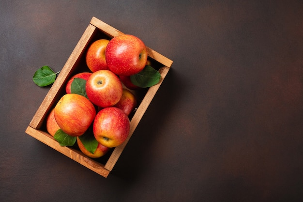 Ripe red apples in wooden box on a rusty background. top view with space for your text.