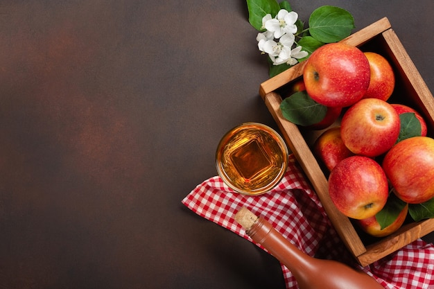 Ripe red apples in wooden box with branch of white flowers, glass and bottle of cider on a rusty background. top view with space for your text.