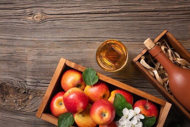 Ripe red apples in wooden box with branch of white flowers, glass and bottle of cider on a wooden table. top view with space for your text.