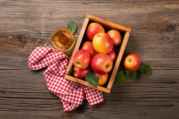 Ripe red apples in wooden box with branch of white flowers and glass of fresh juice on a wooden table. top view with space for your text.