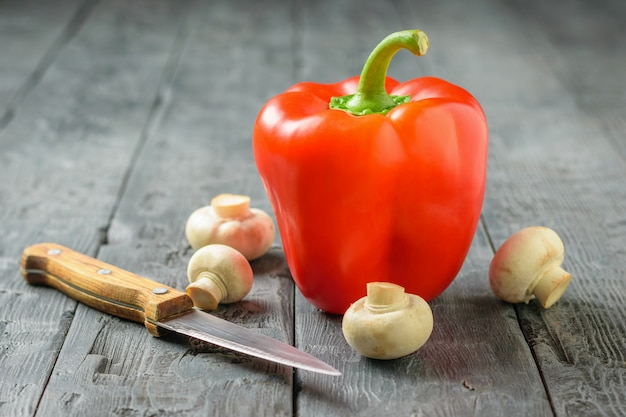 Ripe red bell pepper with mushrooms on a wooden table. vegetarian food.
