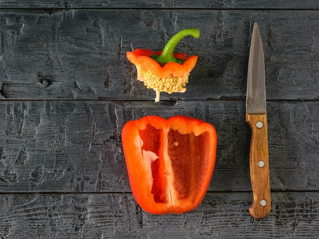 Ripe red bell pepper with mushrooms on a wooden table.