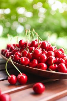 バスケットの木製テーブルに熟した赤いベリー。果物と夏の背景。さくらんぼの収穫。