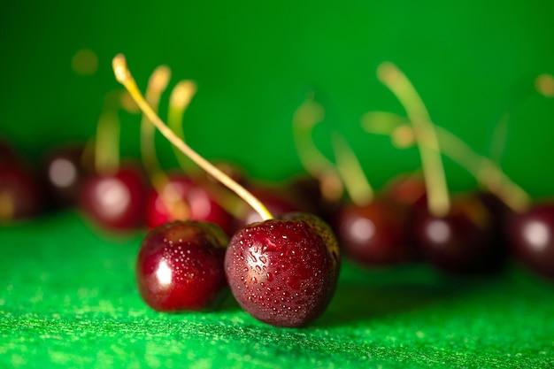Спелая красная вишня на зеленом фоне.