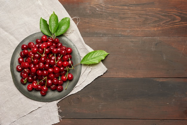 Ripe red cherry in a round metal bowl on a brown wooden space