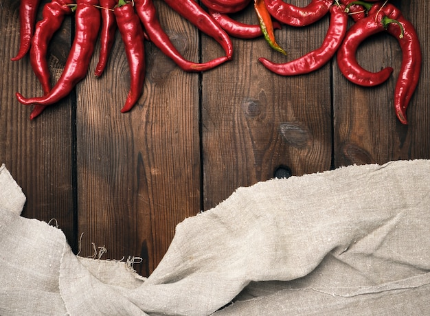 Ripe red chili peppers on a brown wooden vintage background from boards