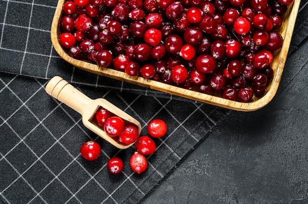 木製のボウルに熟した赤いクランベリー。黒の背景。上面図