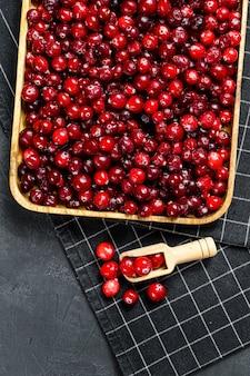 Спелые красные клюквы в деревянной миске. черный фон. вид сверху