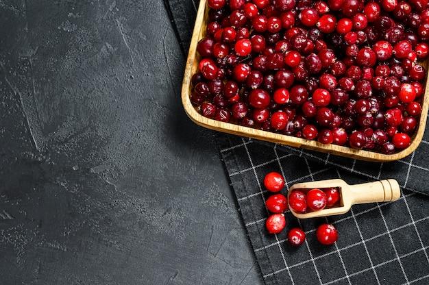 木製ボウルに熟した赤いクランベリー黒い表面