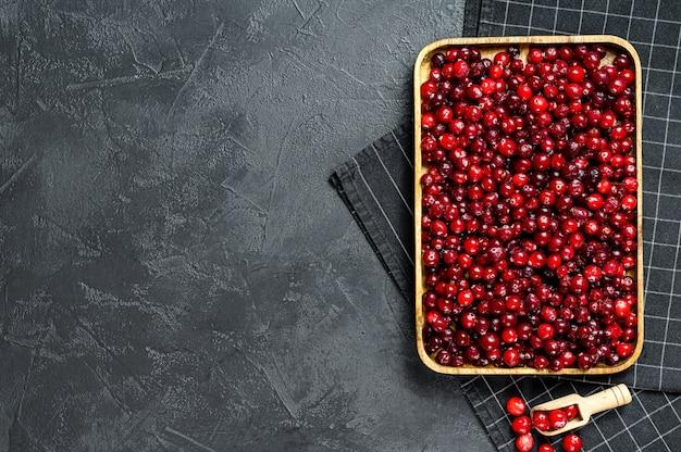 木製のボウルに熟した赤いクランベリー。
