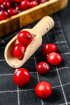 木のスプーンで熟した赤いクランベリー。閉じる。黒の背景。上面図