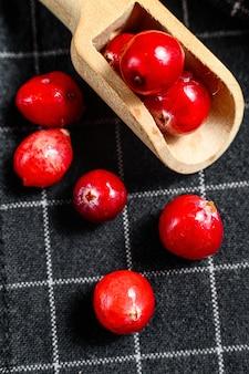 Спелые красные клюквы в деревянной ложкой. закройте черный фон. вид сверху