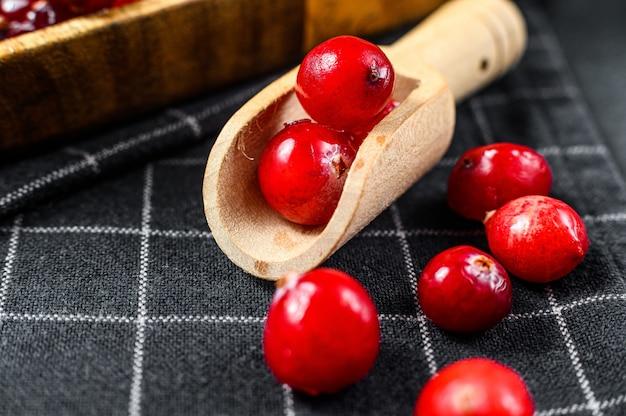 木のスプーンで熟した赤いクランベリーをクローズアップ黒い表面