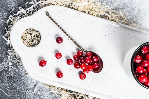 鉄のマグカップで熟した赤いクランベリー。灰色の背景。上面図