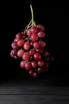Гроздь спелого красного винограда, парящая на черном