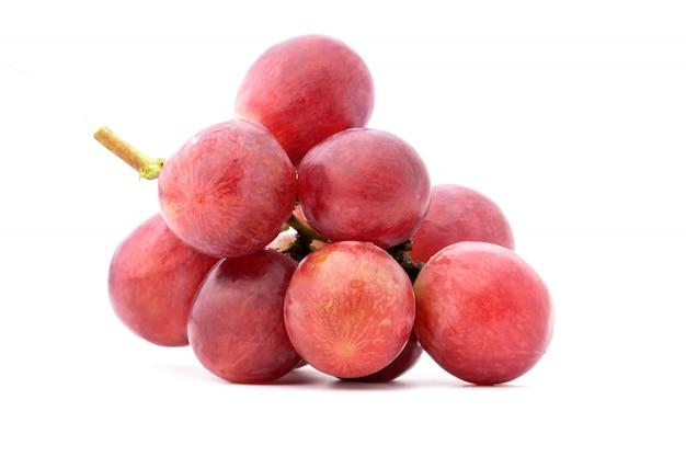 白い表面上に分離されて熟した赤いブドウ