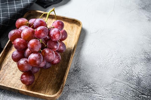 熟した赤いブドウ。熟したブドウのピンクの束。白色の背景
